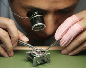 A craftsman examines a watch at the official opening of the Omega Pavilion ahead of the Beijing 2008 Olympic Games August 4, 2008.     REUTERS/Claro Cortes Iv (CHINA)
